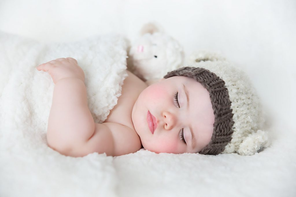 Harrodsburg, KY newborn photographer picture of baby asleep with a lamb bonnet on