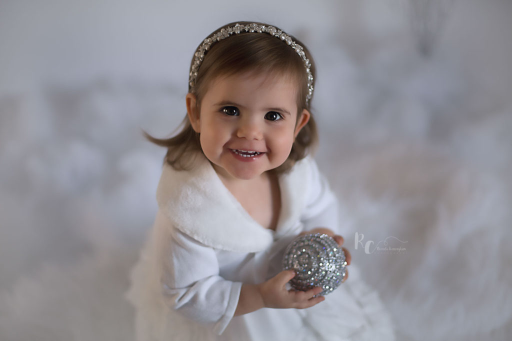 Litter girl holding an ornament in holiday session by Rhonda Cunningham, Lexington Family Photographer.