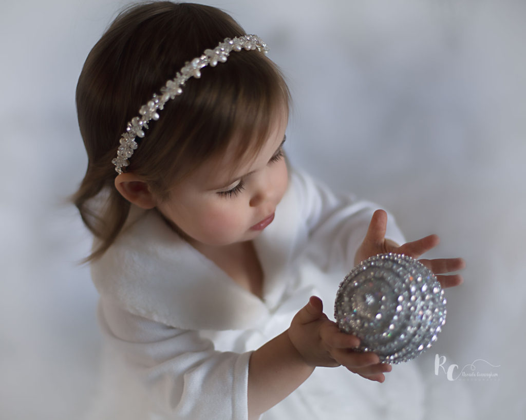 Little girl looking down at an ornament in a winter themed session by Lexington Family Photographer, Rhonda Cunningham.