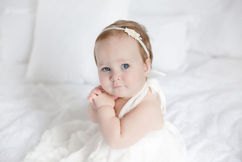 baby girl in white dress sitting on white bed during her one year portrait session by Rhonda Cunningham Photography, Lexington Ky baby photographer