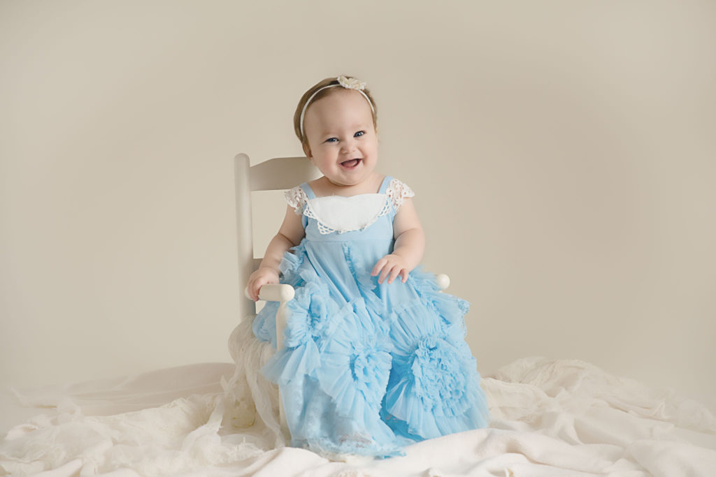 Portrait of a one year old in a blue dress sitting in a rocking chair during her Lexington, KY cake smash session by Lexington Ky baby photographer