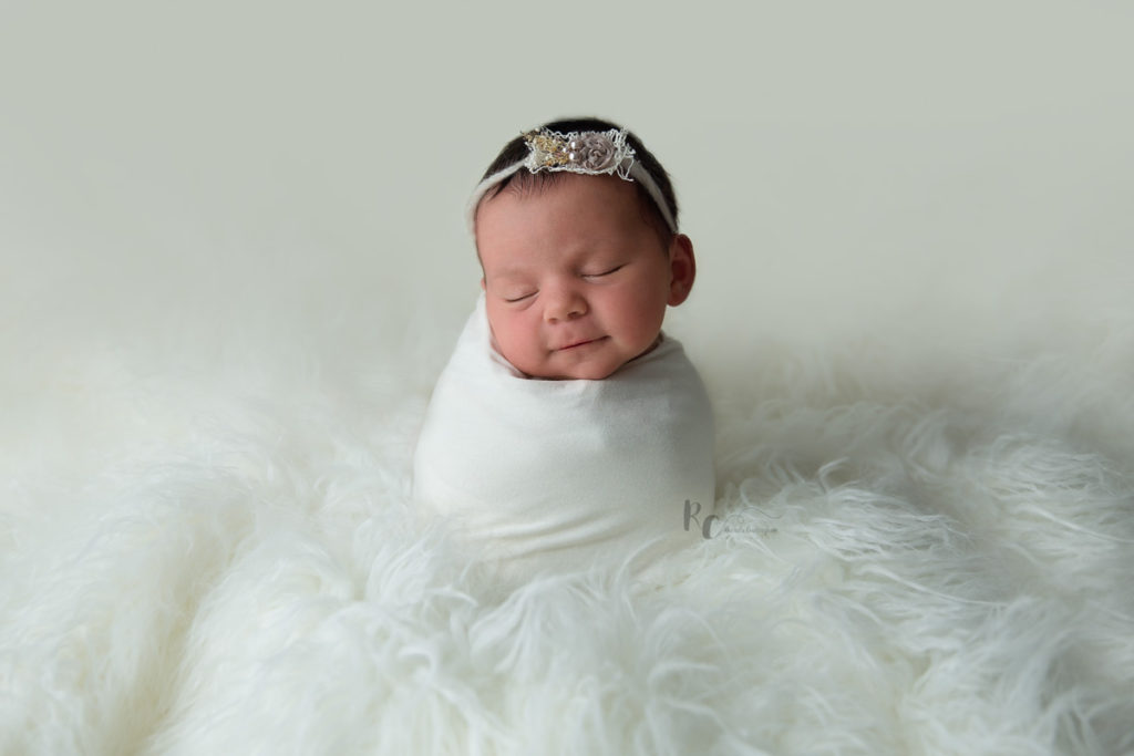 Newborn portrait of baby swaddled and sitting upright in cream fur by Lexington Ky Newborn Photographer Rhonda Cunningham Photography.