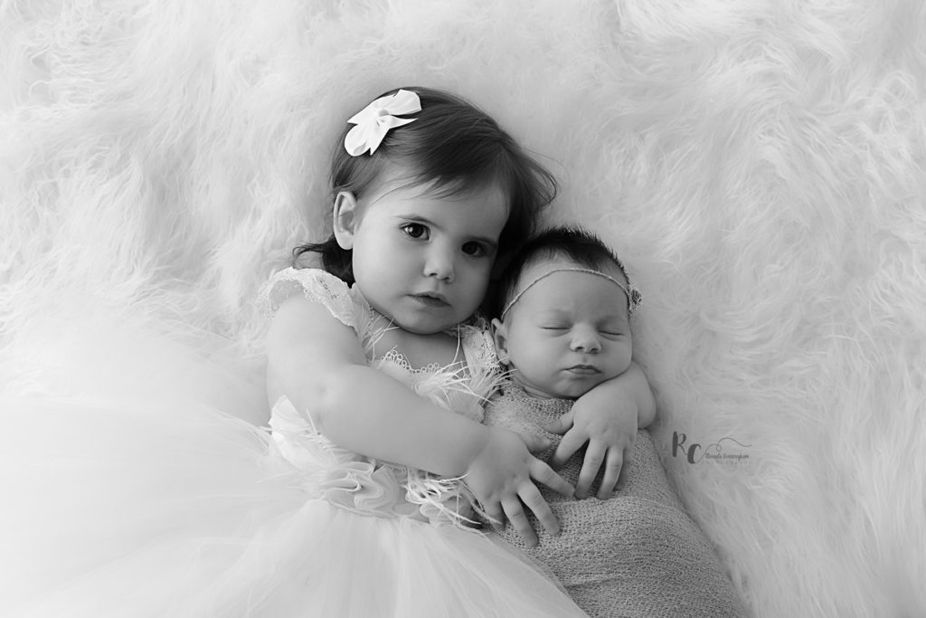 two year old hugging newborn sister in black and white by Rhonda Cunningham Photography, Lexington Ky newborn photographer