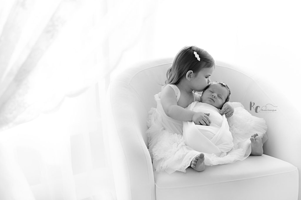 Black and white photo of 2 year old kissing her baby sister by lexington ky newborn photographer Rhonda Cunningham photography