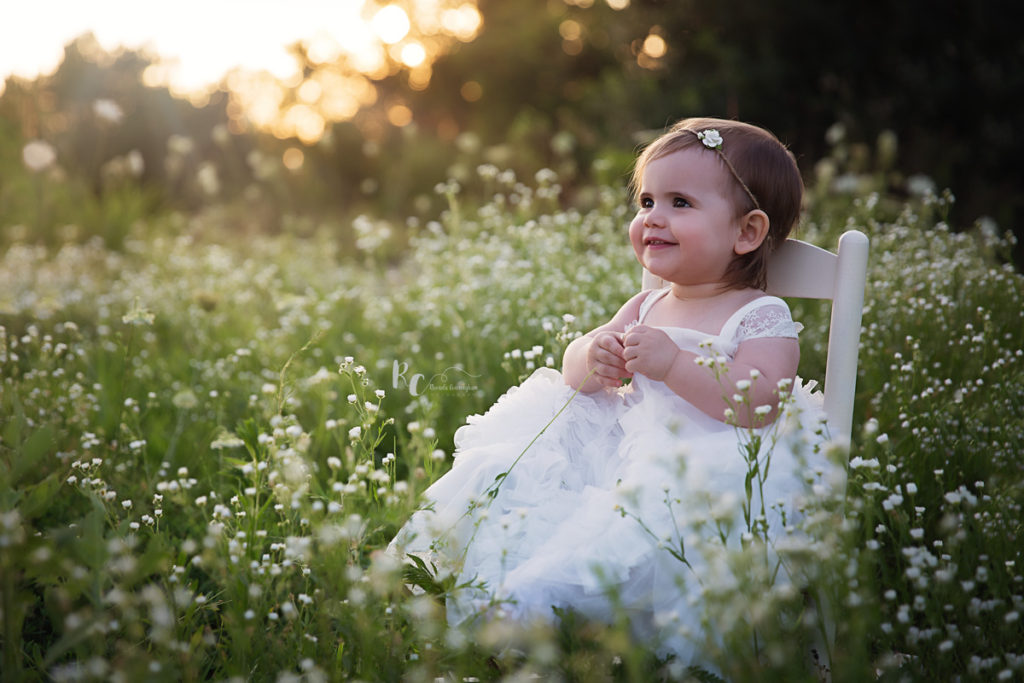 outdoor one year portrait session of baby girl in wildflowers by lexington ky newborn photographer rhonda cunningham photography